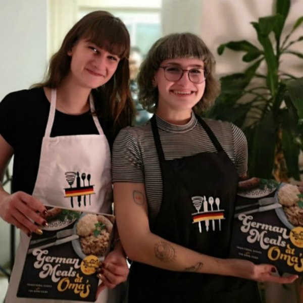 Lydia and Alana showing off their new aprons and cookbooks.