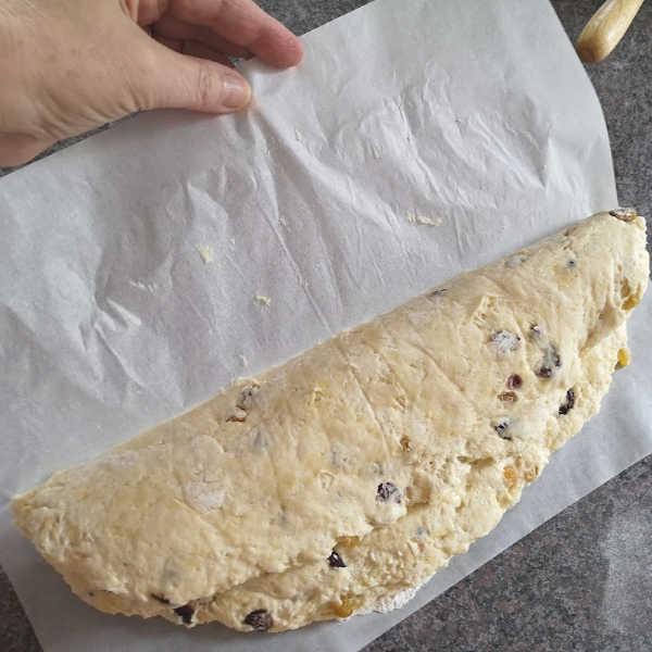 German Quark Stollen: Pull  back parchment paper from Stollen dough #stollen #christmas #germanrecipes #justlikeoma https://www.quick-german-recipes.com/stollen-recipe.html