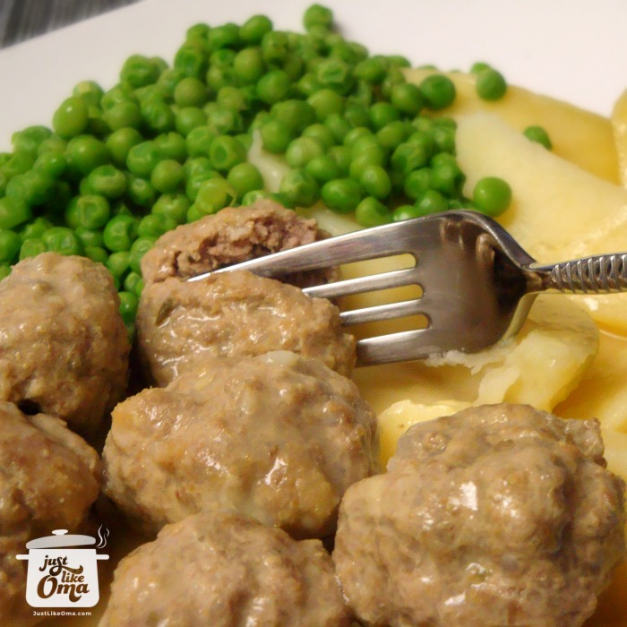 a white plate with Königsberger Klopse mit Hollandische Sosse (saucy meatballs) with boiled potatoes and peas