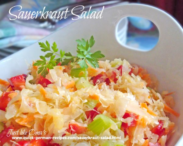 White bowl filled with sauerkraut salad consisting of sauerkraut, red and yellow peppers and a dressing