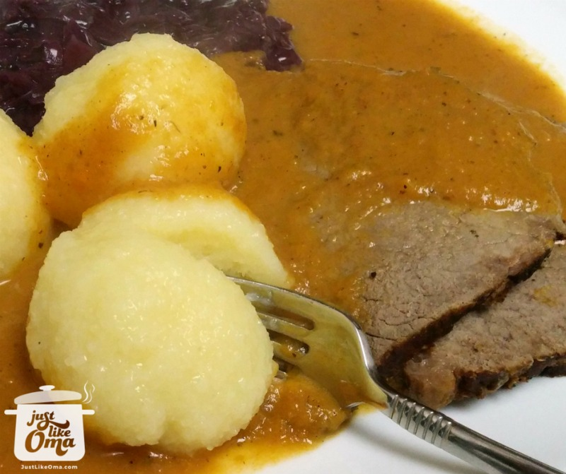 slow cooker pot roast served with potato dumplings and red cabbage with lots of gravy