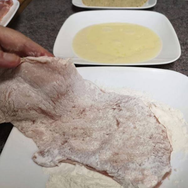 Dredging the schnitzel in flour, then egg, then bread crumbs