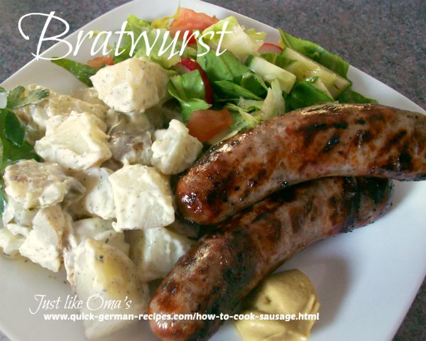 plate of pork sausages and German potato salad with mustard on the side