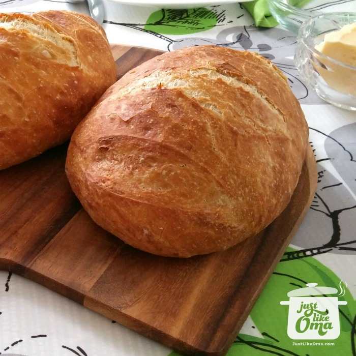 Wooden cutting board with two no knead artisan bread on a white/green tablecloth