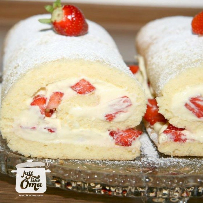 Two Cream Rolls filled with whipped cream and fresh red strawberries on a crystal plate