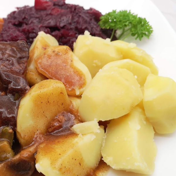 Plate of boiled potatoes, ham hocks, and sauerkraut salad