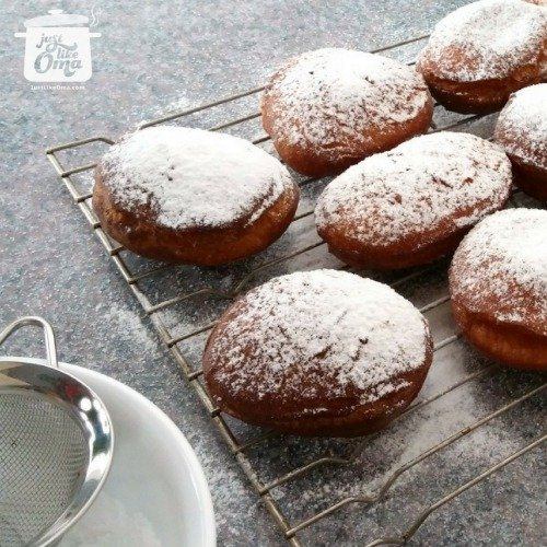 sieving powdered sugar over jelly donuts