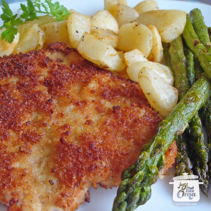 White plate with Schnitzel, fried potatoes, and roasted asparagus