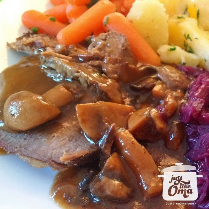 Plate with slow cooked roast beef (tastes like rouladen) with potatoes, buttered carrots and sweet and sour red cabbage with a mushroom gravy.